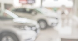 blur image of Commercially cars stand in show room of car shop.