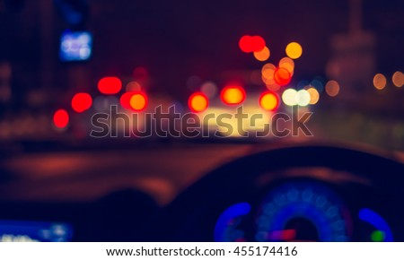 blur image of inside cars with bokeh lights with traffic jam on night time for background usage. (vintage tone)