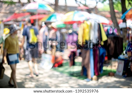 Blur image of outdoor market in the garden, green tree and people background.