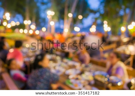 blur image of restaurant and flower in the garden night time for background usage.