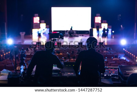 Blur image of sound engineer backstage crew team working to setting and preparing production for show events or music concert stage with blurry white screen in background.