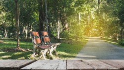 blur image of wood bench for resting and relaxing beside walkway in the park with selected focus empty wood table for display your product