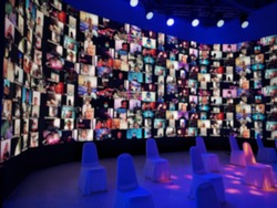 Blur large LED screen show many people's faces join big online event or virtual reality live conference. Video conference, Work from home, Social distancing, New normal event production.