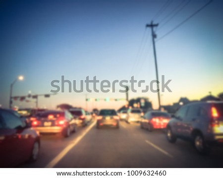 Blur long line cars waiting at stop light in Irving, Texas, USA. Rear view red brake. Typical scene of traffic jam busy road during rush hour sunset. Abstract transportation background. Vintage tone