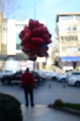 blur man selling balloons at street