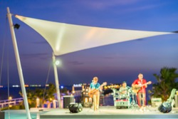 Blur music band performing on stage with reflection on swimming pool beside the beach
