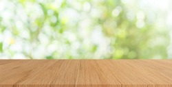 blur nature panoramic background with glow sunny light and modern plain wood table top perspective view for promote product concept.