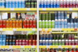 Blur of bottles of beer, cider and other alcohol drinks on Shelf in Supermarket Liquor Part