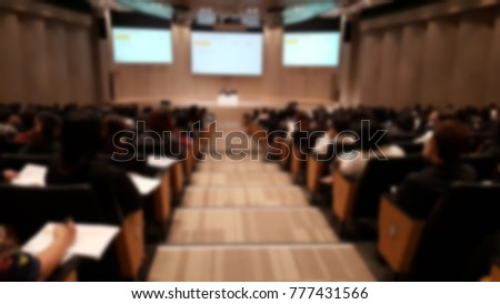 Blur of many company worker training and taking note in conference hall while speaker teaching at front of stage with three big projector background. Employee learning and development by HR concept.