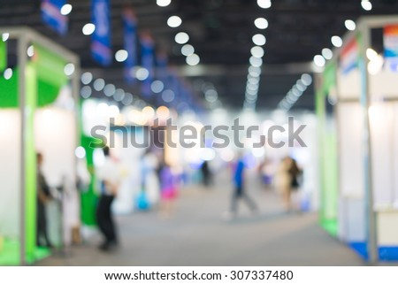 Blur of people in exhibition hall event.