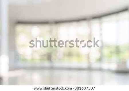 Blur office building, healthcare clinic, hospital or school background interior view looking out toward to empty lobby and entrance doors and glass curtain wall