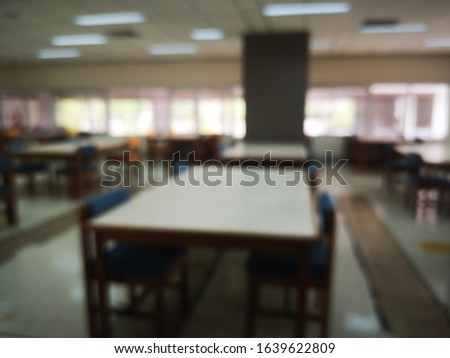 Blur or bokeh Interiors design wooden chairs and tables in the library room of university with the shelf books but nobody in the morning