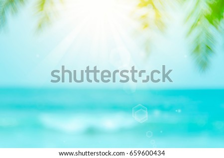 Blur palm leaf on beach with bokeh wave sun light abstract background.