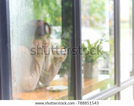 Blur portrait of Asian woman sitting in glass house cafe drinking hot coffee latte with green fresh tree background