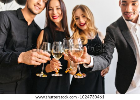 Blur portrait of cute curly woman and her friends with wineglasses on foreground. Fair-haired european female model celebrating new year with colleagues in office. #1024730461