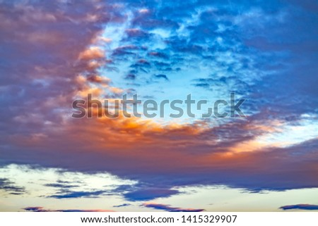 Blur skyscape with thick gray clouds filling the boundless sky at sunset #1415329907