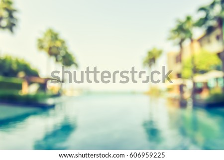 Blur summer background for resort hotel swimming pool party with blue cool sky and tropical palm tree #606959225