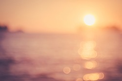 Blur sunset beach with bokeh sun light wave abstract background. Travel concept. Retro color style.