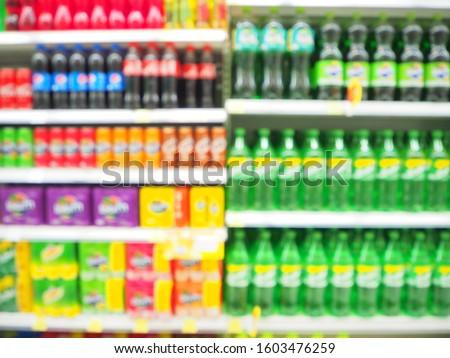 Blur Supermarket sale Soda pop drinks and soft drinks section on shelves background, Many Soda pop drinks and soft drinks sale on the shelf in a supermarket, as blurred effect background.