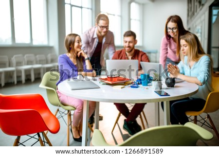 Blur Team of a young coworkers dressed casually working together with laptops sitting at the round table in the office