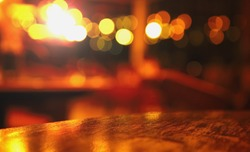 blur top of wood table at pub with bokeh light in the dark night background