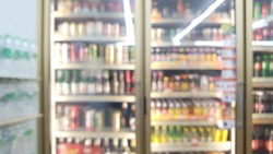 blur view of beverage displayed in refridgerators in convenience store with pure water bottle packs on the left. image of beverage cooler in market.