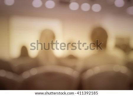 Blur vintage  image style of audience in classroom or auditorium with screen, brown color