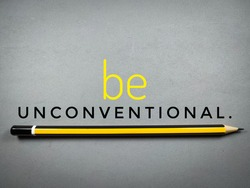 Blur word BE UNCONVENTIONAL with blur pencil.For fashion shirts,poster,gift,or other printing press.Motivation quote.Shot were noise and film grain.