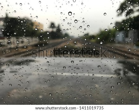 Blured background with rains drop on glass and cars on the railway, Road view through railway window blurry with heavy rain, Driving in rain, rainy weather