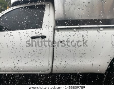 Blured background with rains drop on glass and cars on the road, Road view through car window blurry with heavy rain, Driving in rain, rainy weather