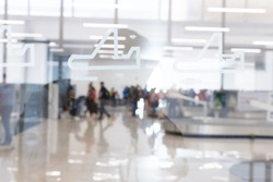 Blured image of people waiting for their suitcases on luggage conveyor belt in the baggage claim at airport arrival hall. Airline traveling concept.