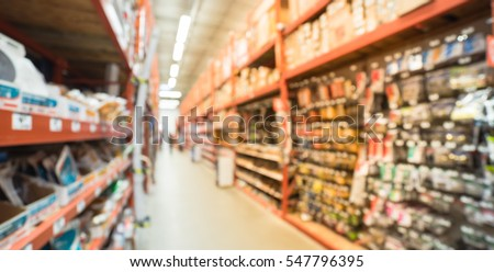 Blurred a large hardware store, tools and material. Defocused interior of home improvement retailer, racks of door hardware, weather proofing and lockset floor to ceiling. Customers shopping. Panorama