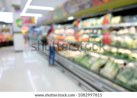 Blurred a woman choosing foods in supermarket store at shopping mall background, stock of product on the shelves of whole foods and drinks market.