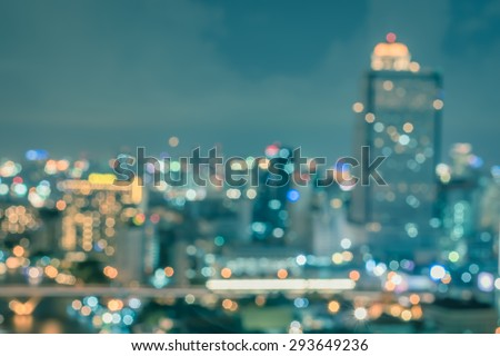 Blurred abstract background aerial view of Bangkok downtown city night lights with colorful bokeh in cool vintage cyan turquoise blue tone: Central business district on electric train line over river