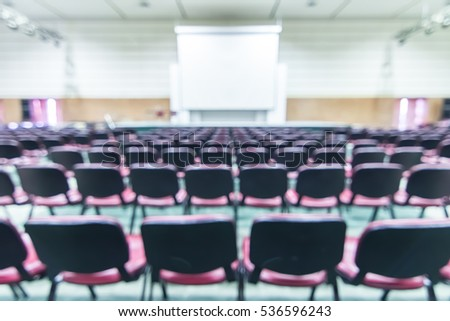 Blurred abstract background empty business/ educational conference seminar in auditorium hall with no audience students sitting in seat rows and presenters on stage with projector screen presentation