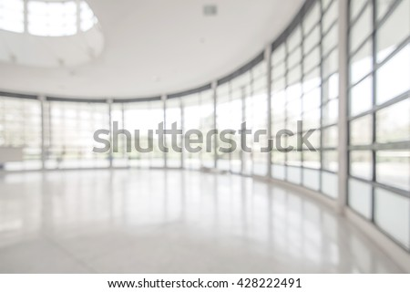 Blurred abstract background exterior view looking out toward to empty office lobby and entrance doors and glass curtain wall with frame: Blurry perspective of reception hall to building entry/ exit