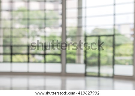 Blurred abstract background interior view looking out toward empty vacant office lobby and entrance doors and glass curtain wall frame: Blurry perspective of reception hall to building main entrance