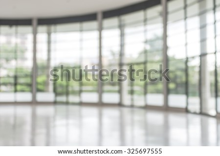 Blurred abstract background interior view looking out toward to empty office lobby and entrance doors/ glass curtain wall with frame: Blurry perspective of reception hall to public building entrance
