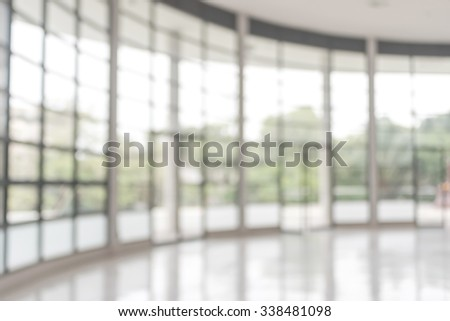Blurred abstract background interior view looking out toward to empty office lobby and entrance doors and glass curtain wall with frame: Blurry perspective of reception hall to building entrance