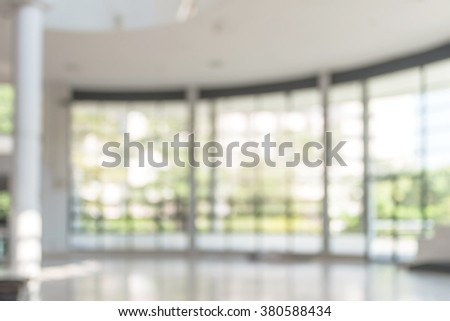 Blurred abstract background interior view looking out toward to empty office lobby and entrance doors and glass curtain wall with frame: Blurry perspective of reception hall to building entry/ exit