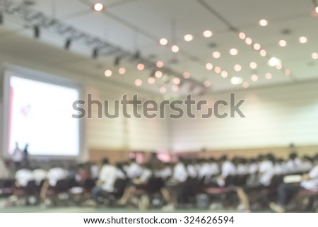 Blurred abstract background of business/ educational conference and seminar in auditorium hall with audiences/ students sitting in seat rows and presenters on stage with projector screen presentation