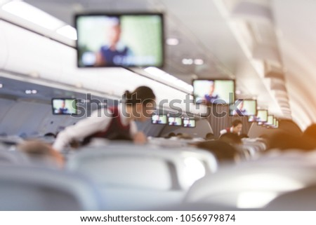 Blurred abstract background of Flight attendant serving passengers on the plane. - Shutterstock ID 1056979874