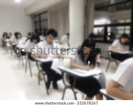 Blurred abstract background of group of asian students having mid-term examination in school: Blurry view  inside class of university/ college students sitting in rows doing final exam in classroom