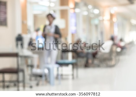 Blurred abstract background of hospital interior waiting hall/ corridor with patient on wheelchair in front of nurse station and OPD - out patient clinic department: Blurry view clinical indoor space