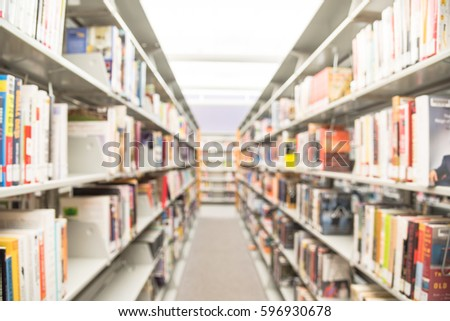 Blurred abstract background of modern public American library interior with aisle of bookshelf with textbooks, literature, thesis, magazines. Self-study, educational concept and background #596930678