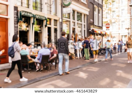 Blurred abstract background of outdoor cafe in Amsterdam. Outdoor cafe with tables, chairs and tourist at the old town.