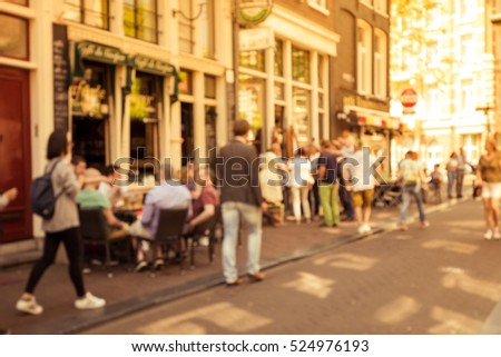 Blurred abstract background of outdoor cafe or restaurant in Amsterdam. Outdoor cafe with tables, chairs and tourist at the old townin golden time.