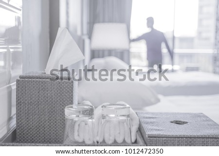 Blurred abstract background of people live in white room that has white bed, white pillow,white blanket, white wall. It is a very comfortable room. There are glasses and towel preparing on table.