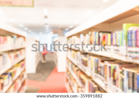 Blurred abstract background of public library interior with aisle of bookshelf with textbooks, literature, magazines. Female student is selecting books from bookshelf. Self-study education concept