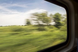 blurred abstract green landscape seen from a window train in motion - summer in Missouri